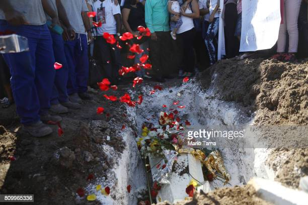 Rose petals are tossed as mourners gather during the burial of Vanessa dos Santos who was shot in the head and killed in the doorway of her house...