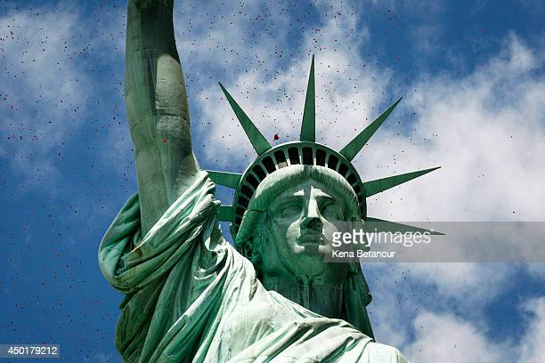 Rose petals drop over the Statue of Liberty during the Commemorating 70th Anniversary of DDay on June 06 2014 in New York City Three helicopters have...