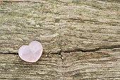 rose quartz heart on wooden ground