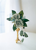 Rose, raspberry and baby's breath arranged in gold vase by window