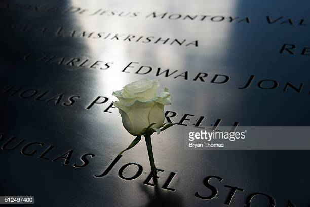 A rose stands in an engraved name on the parapet of the 9/11 Memorial on the 23rd Anniversary of the World Trade Center bombing on February 26 2016...