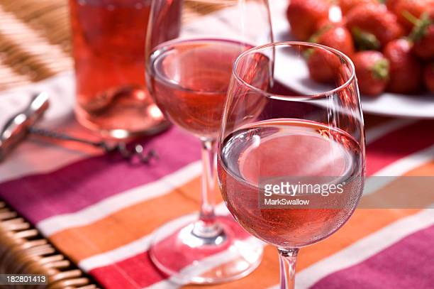 Rose wine picnic with glasses and strawberries