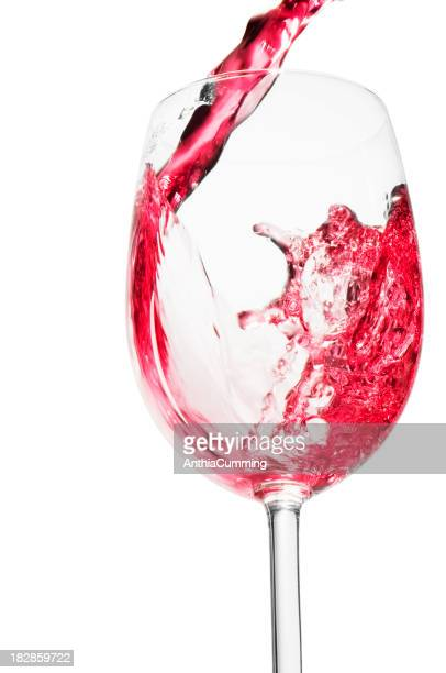 Rose wine pouring into a tall clear wine glass