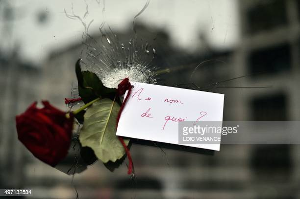 A rose with a sign reading 'In the name of what' is pictured in a bullet hole in the window of a Japanese restaurant next to the cafe 'La Belle...