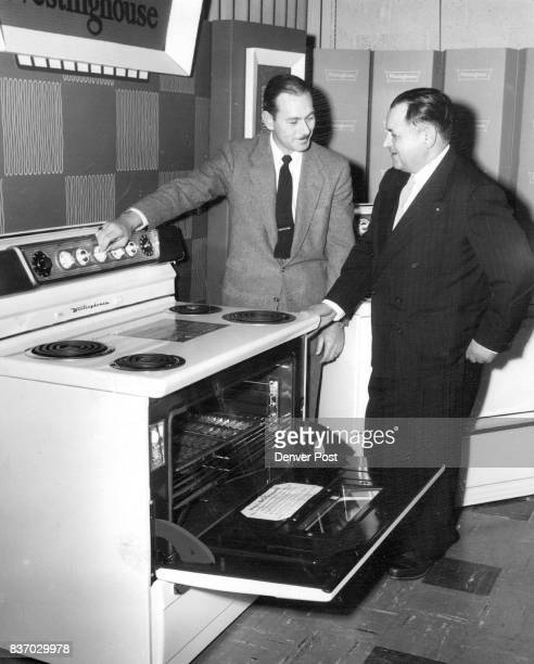 R H Roseberry assistant sales manager for McCollum Law Corp shows Sam Smith Laramie Wyo appliance dealer the 1955 Westinghouse electric range model...