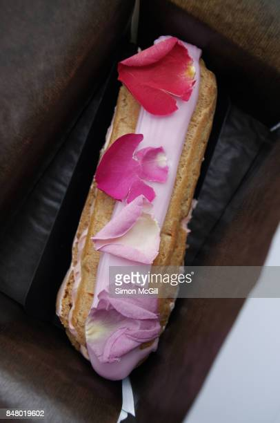 Rose-flavoured eclair in a white cardboard take out box