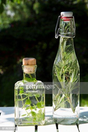Rosemary and oregano vinegar in glass bottles