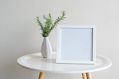 Close up of sprigs of rosemary in small white vase with blank square frame on round table against beige wall