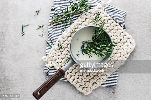 Rosemary infusing in saucepan of milk