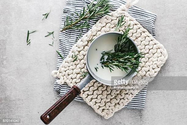 Rosemary infusing in saucepan of milk