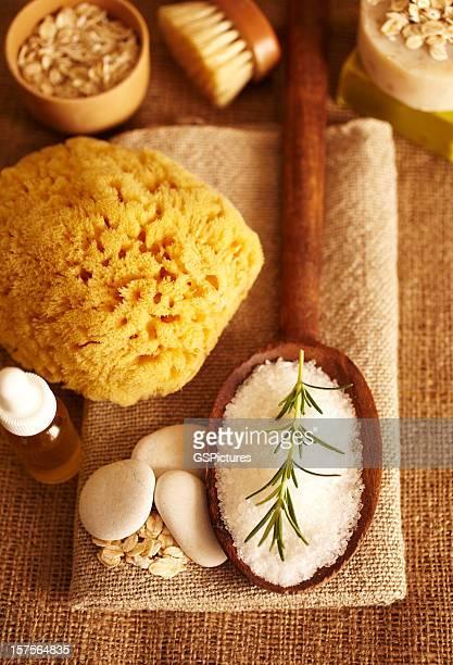 Rosemary on bath salt scrub in wooden spoon and oil