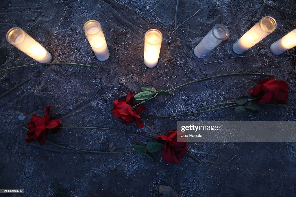 Roses and candles are seen in a memorial setup near the Inland Regional Center on December 5 2015 in San Bernardino California Police continue to...