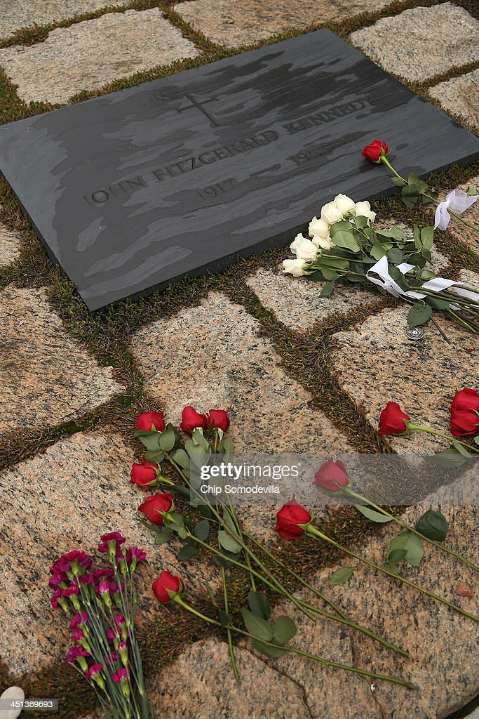Roses and other flowers left by family members and admirers lay on the ground next to former U.S. President John F. Kennedy's grave marker at Arlington National Cemetery November 22, 2013 in Arlington, Virginia. Remembrance ceremonies will be held arcoss the United States today, the 50th anniversary of the assisination of President Kennedy.