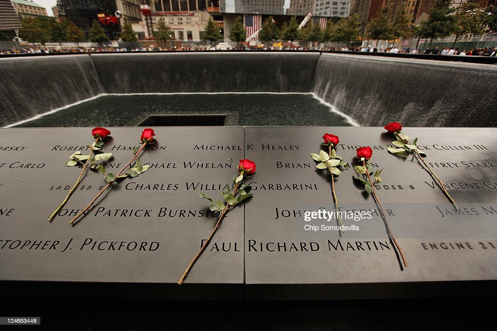 Roses are left on the bronze plaques that bear the names of the victims of the September 11 terror attacks that surround the perimeter of the 9/11...