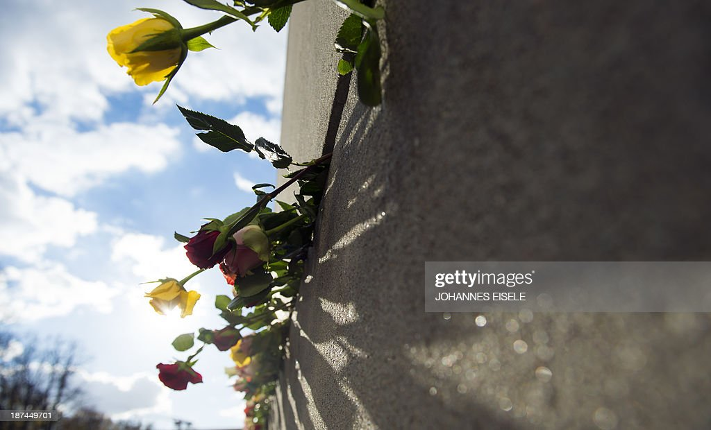Roses are placed in a preserved segment of the Berlin Wall at Bernauer street on November 9, 2013 in Berlin on the 24th anniversary of the fall of the Wall.