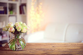 bouquet of roses in a vase standing on a table in an interior room