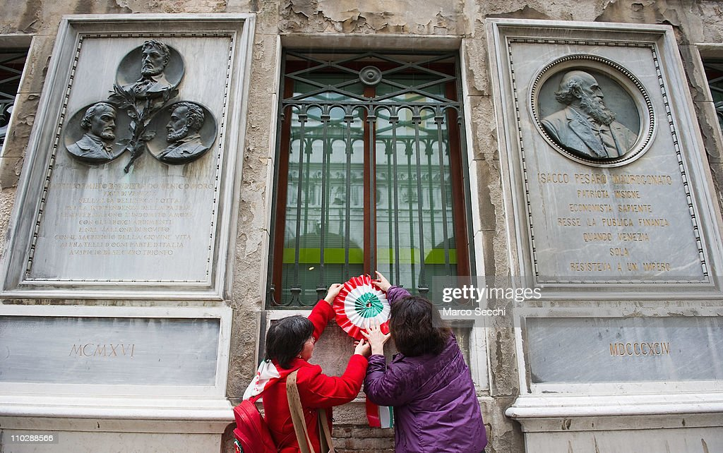A rosette with the colours of the Italian national flag is hang under the stone commemorating martyrs of the Risorgimento on the day of the celebrations for the 150th anniversary of Italy's unification on March 17, 2011 in Venice, Italy. Events in various Italian cities will celebrate the 150th anniversary of Italy's unification until the end of the year. National Festivity begins on March 17.