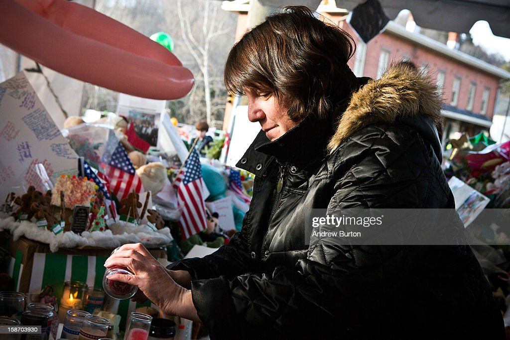 Rosina Zaretzky lights a candle at a memorial for those killed in the school shooting at Sandy Hook Elementary School, on December 24, 2012 in Newtown, Connecticut. Donations and letters are pouring in from across the country as the town tries to recover from the massacre.