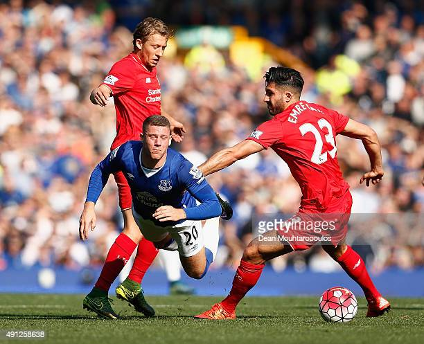 Ross Barkley of Everton is tripped by Emre Can of Liverpool and Lucas Leiva of Liverpool during the Barclays Premier League match between Everton and...