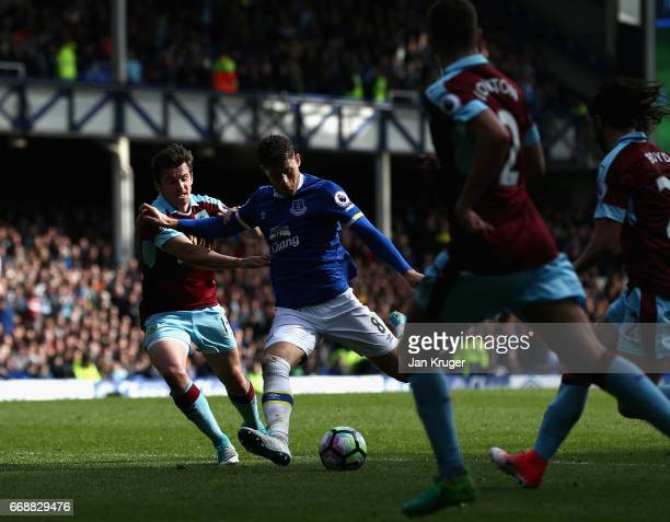Ross Barkley of Everton shoots and his shot is deflected into the goal by Ben Mee of Burnley for Everton's second goal during the Premier League...