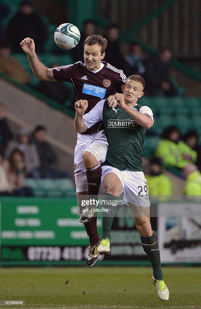 Ross Caldwell of Hibernian tackles Andy Webster of Hearts during the Scottish Cup match between Hibernian and Hearts at Easter Road Stadium on December 2, 2012 in Edinburgh,Scotland.