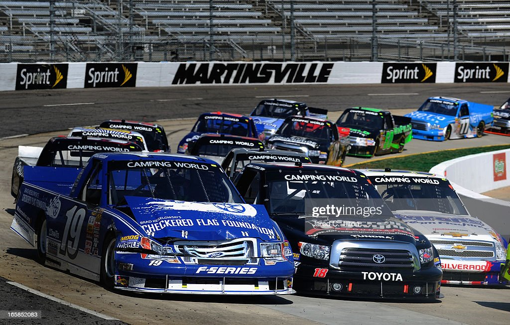 Ross Chastain, driver of the #19 Brad Keselowski's Checkered Flag Foundation , Joey Coulter, driver of the #18 Darrell Gwynn Foundation Toyota, and Chase Elliott, driver of the #94 Aaron's Dream Machine/Hendrickcars.com Chevrolet, races three wide out of turn four during the NASCAR Camping World Truck Series Kroger 250 on April 6, 2013 at Martinsville Speedway in Ridgeway, Virginia.