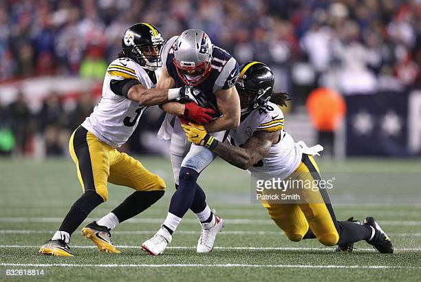 Ross Cockrell and Bud Dupree of the Pittsburgh Steelers attempt to tackle Julian Edelman of the New England Patriots in the AFC Championship Game at...