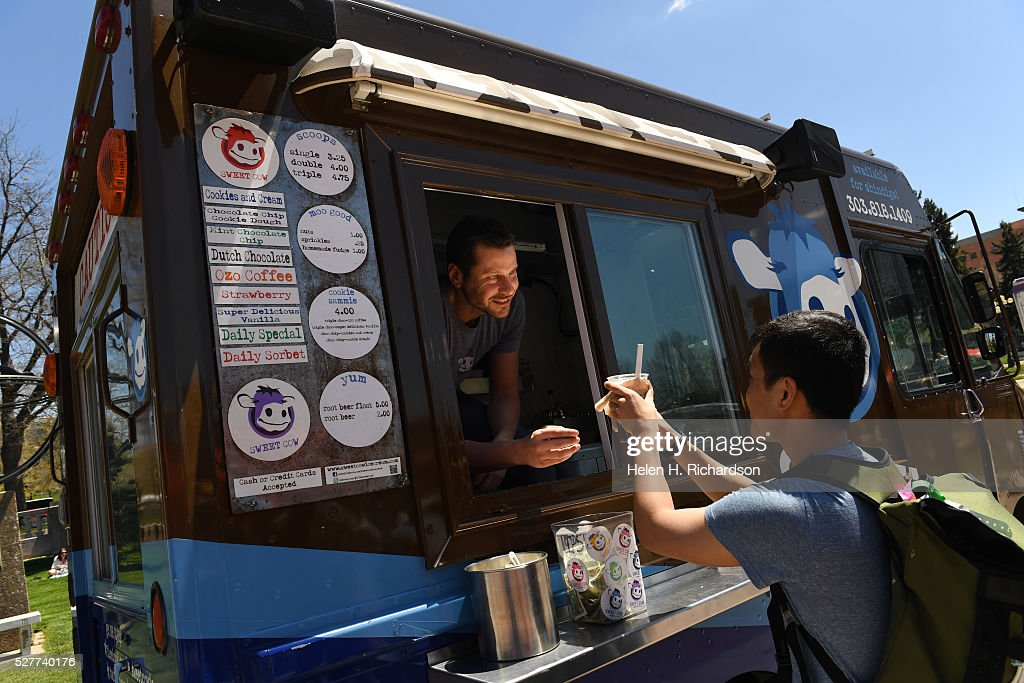 Ross Cohen, left, owner of Sweet Cow Ice Cream truck, gives a delicious cup of homemade ice cream to a customer at Civic Center Park on the first day of the 11th annual Civic Center EATS on May 3, 2016 in Denver, Colorado. This is metro Denver's largest gathering of gourmet food trucks and carts and is a showcase of Denver's culinary and entrepreneurial diversity. The daily food truck lunch event runs through October 6th from 11 am to 2 pm Tuesdays, Wednesdays and Thursdays.