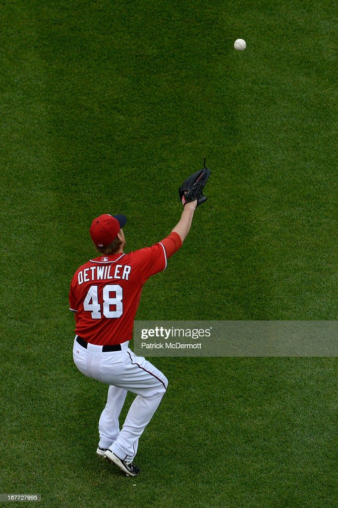 <a gi-track='captionPersonalityLinkClicked' href=/galleries/search?phrase=Ross+Detwiler&family=editorial&specificpeople=4329174 ng-click='$event.stopPropagation()'>Ross Detwiler</a> #48 of the Washington Nationals fails to catch a single hit by Corky Miller #37 of the Cincinnati Reds in the fourth inning of a game at Nationals Park on April 28, 2013 in Washington, DC.
