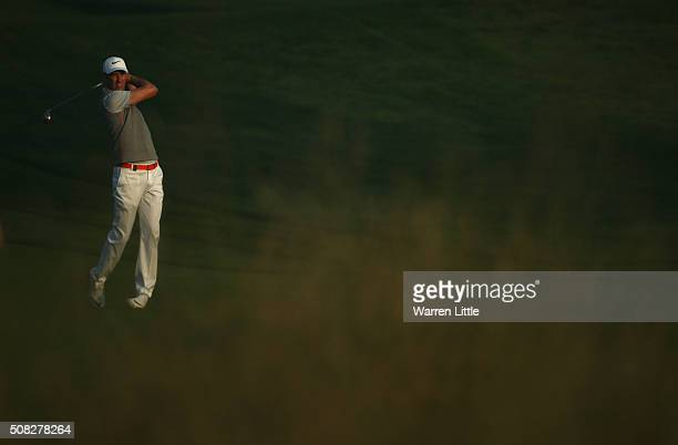 Ross Fisher of England plays his seocnd shot into the 10th green during the first round of the Omega Dubai Desert Classic on the Majlis course at the...