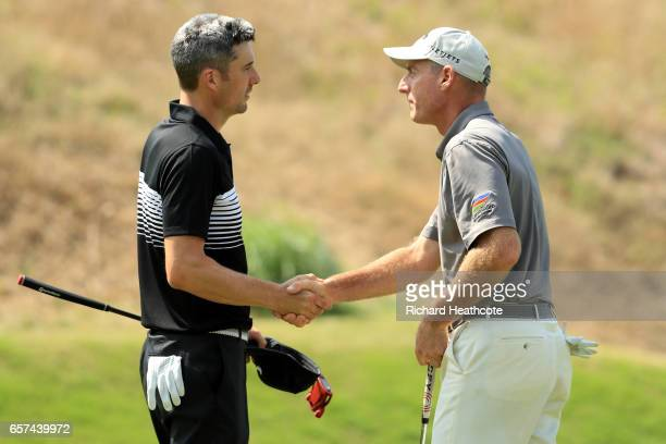 Ross Fisher of England shakes hands with Jim Furyk after winning their match 32 on the 16th hole during round three of the World Golf...