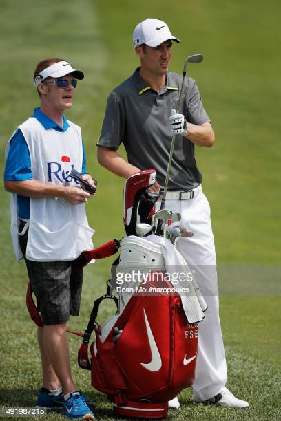 Ross Fisher of England speaks to his caddie and selects a club before he hits his second shot on the 1st hole during the final round of the Open de...