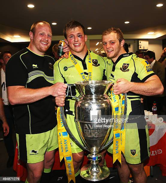 Ross McMillan Alex Waller and Mike Haywood of Northampton Saints celebrate with the trophy following victory in the Aviva Premiership Final between...