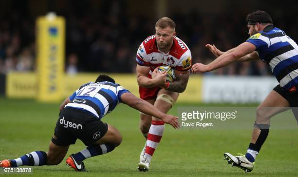 Ross Moriarty of Gloucester is tackled by Ben Tapuai and Nathan Catt during the Aviva Premiership match between Bath and Gloucester at the Recreation...