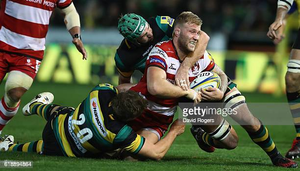 Ross Moriarty of Gloucester is tackled by Jamie Gibson and Michael Paterson during the Aviva Premiership match between Northampton Saints and...