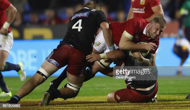 Ross Moriarty of the Lions is tackled by Josh Goodhue and Sam Anderson Heather during the match between the New Zealand Provincial Barbarians and the...