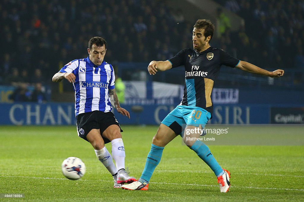 Ross Wallace of Sheffield Wednesday scores the opening goal despite the challenge from Mathieu Flamini of Arsenal during the Capital One Cup fourth...
