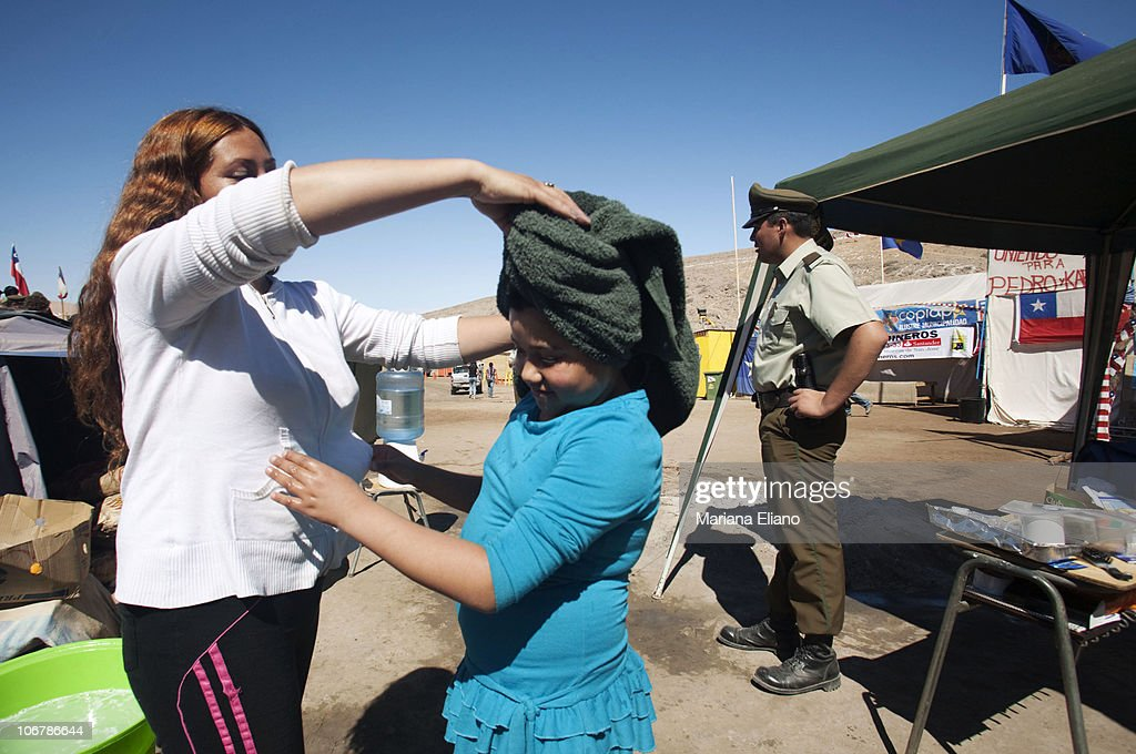 Rossana Gomez daugher of trapped miner Mario Gomez dries the hair of her daughter at Campamento Esperanza at the San Jose Mine in September 2010 near...