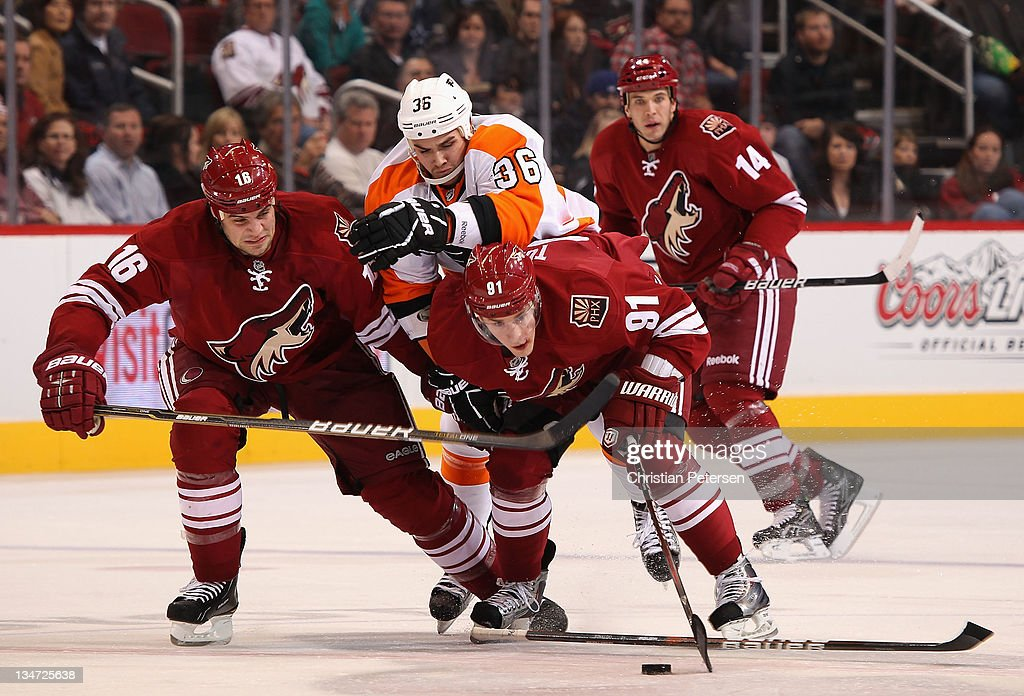 Rostislav Klesla and Kyle Turris of the Phoenix Coyotes attempt to control the puck as Zac Rinaldo of the Philadelphia Flyers skates in during the...