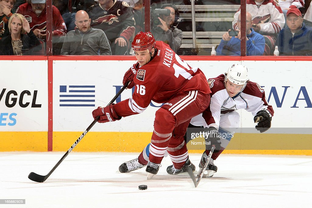 Rostislav Klesla #16 of the Phoenix Coyotes and Jamie McGinn #11 of the Colorado Avalanche skate for a loose puck during the third period at Jobing.com Arena on April 6, 2013 in Glendale, Arizona.