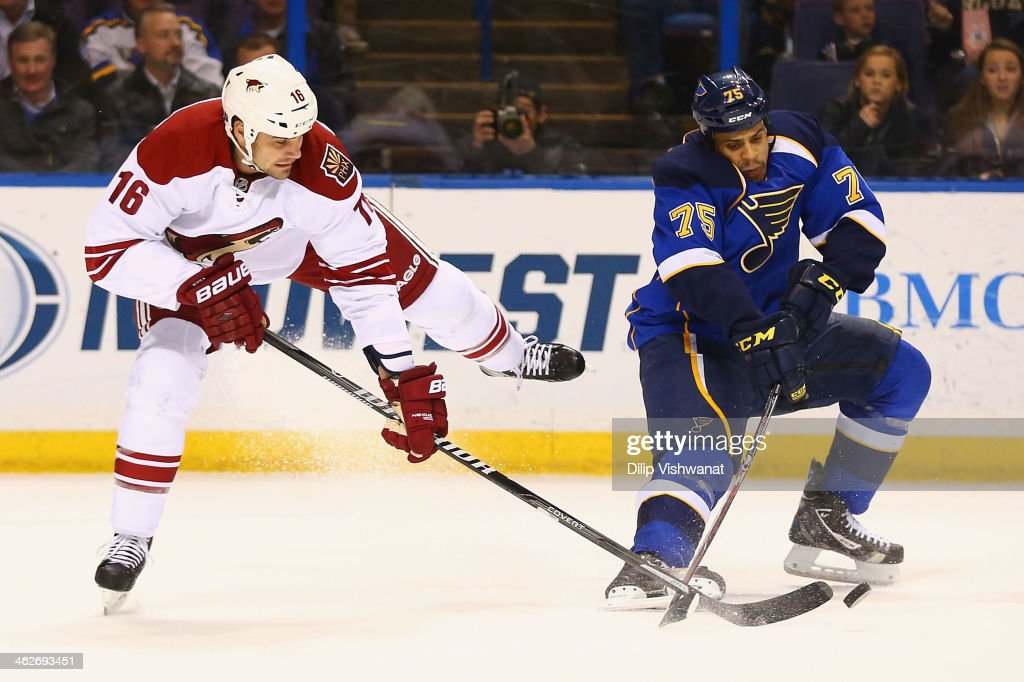 Rostislav Klesla of the Phoenix Coyotes and Ryan Reaves of the St Louis Blues look to control a loose puck at the Scottrade Center on January 14 2014...