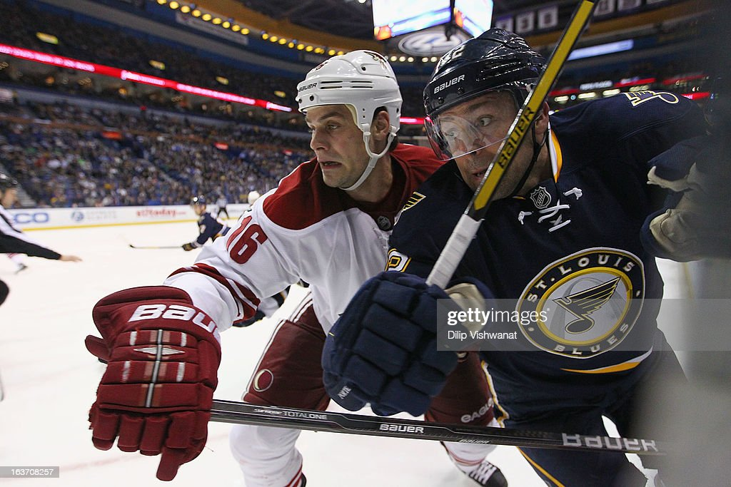 Rostislav Klesla of the Phoenix Coyotes battles Scott Nichol of the St Louis Blues along the boards at the Scottrade Center on March 14 2013 in St...