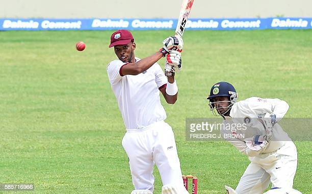 Roston Chase of West Indies connects for a four off a delivery from bowler Ravichandra Ashwin of India as wicket keeper Wriddhiman Saha plays close...