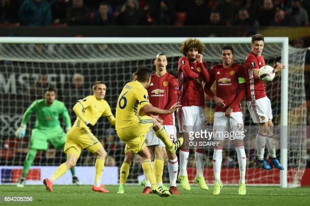 TOPSHOT Rostov's Ecuadorian midfielder Christian Noboa curls a last minute free kick around the Manchester United defensive wall composed of...