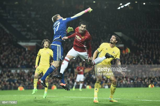 Rostov's Russian goalkeeper Nikita Medvedev punches the ball as he vies with Manchester United's Armenian midfielder Henrikh Mkhitaryan during the...