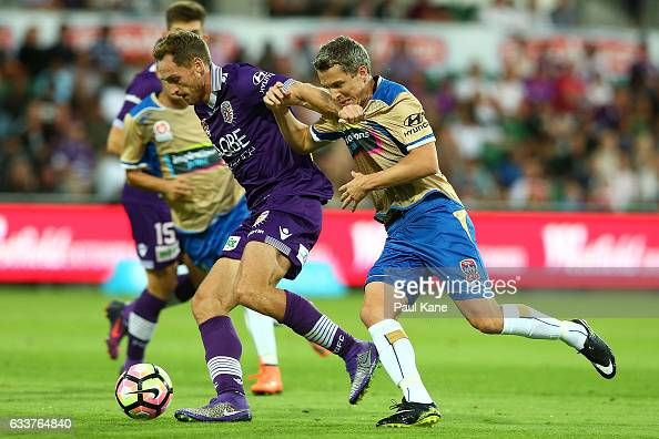 Rostyn Griffiths of the Glory holds off Morten Nordstrand of the Jets in a contest for the ball during the round 18 ALeague match between the Perth...