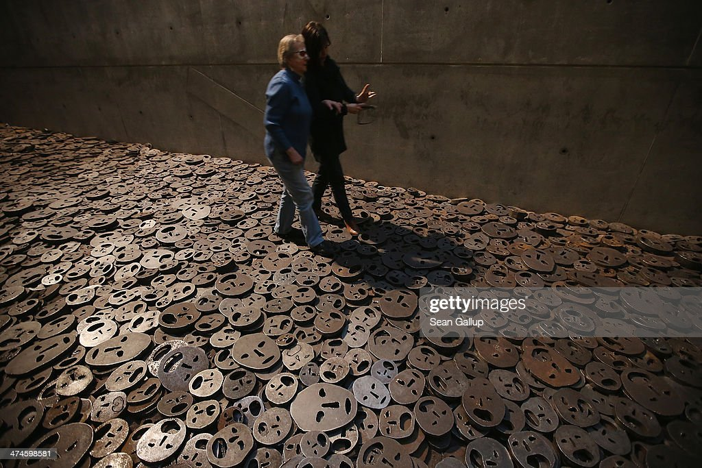 Roswitha Roeding (L), who is blind, and friend Annette Mueller walk among the thousands of metal faces of the work 'Fallen Leaves' by Israeli artist Menashe Kadishman on the first organized architectural tour of the museum for blind people at the Jewish Museum Berlin on February 21, 2014 in Berlin, Germany. The tours, which will be offered four times a year but can also be booked on other occasions, are geared specifically to what a blind person would be most able to appreciate in the building known for its tilted planes and narrowing spaces and designed by American architect Daniel Libeskind.