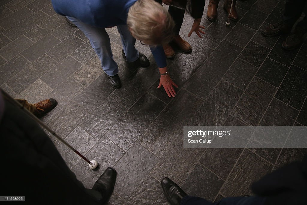 Roswitha Roeding, who is blind, explores the features of the tilted floor with her fingers on the first organized architectural tour of the museum for blind people at the Jewish Museum Berlin on February 21, 2014 in Berlin, Germany. The tours, which will be offered four times a year but can also be booked on other occasions, are geared specifically to what a blind person would be most able to appreciate in the building known for its tilted planes and narrowing spaces and designed by American architect Daniel Libeskind.