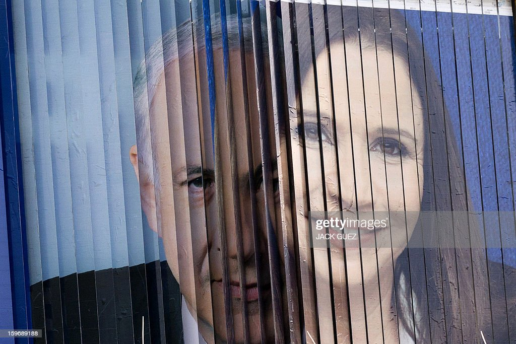 A rotating board shows election campaign posters for Israeli Prime Minister Benjamin Netanyahu (L) and Israeli Labor party leader Shelly Yachimovich (R) on January 18, 2013 in the Mediterranean coastal city of Tel Aviv ahead of the country's general elections on January 22. AFP PHOTO / JACK GUEZ
