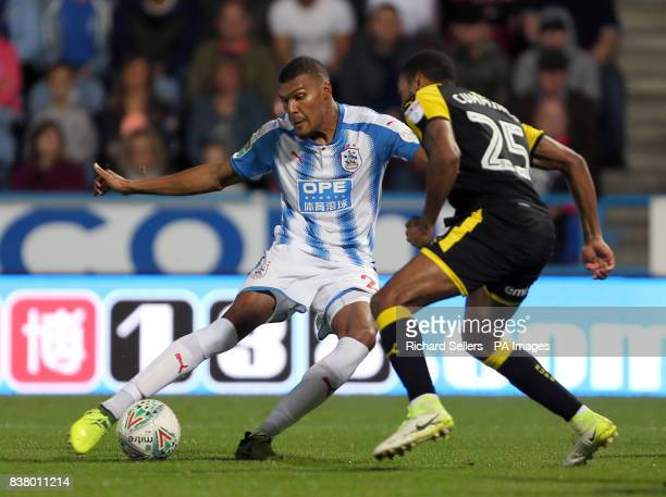 Rotherham United's Shaun Cummings and Huddersfield Town's Collin Quaner battle for the ball during the Carabao Cup Second Round match at the John...